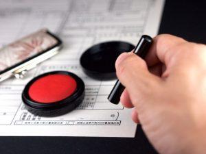 契約書に印鑑を捺す手